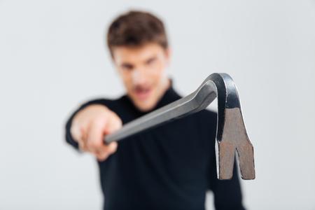 crowbar: Closeup of angry burglar standing and holding crowbar