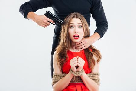 Criminele man zette het pistool naar de tempel van mooie vrouw