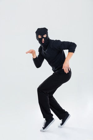 Funny scared criminal young man in balaclava running out Stock Photo