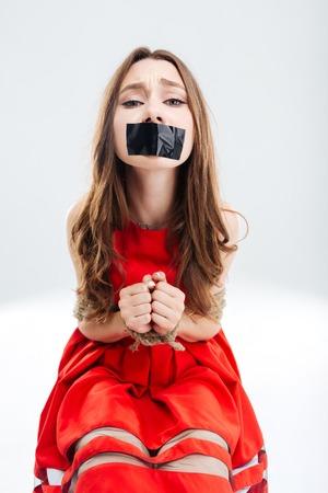 boca cerrada: Mujer delimitado por cuerdas que se sienta con la boca cerrada por la cinta y que pide ayuda