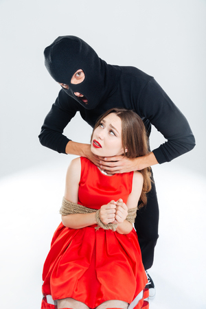 suffocation: Scared young woman bounded with ropes choking by man in balaclava Stock Photo