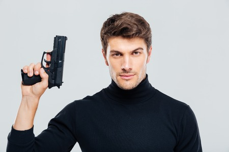 Portrait of handsome young man holding a gun