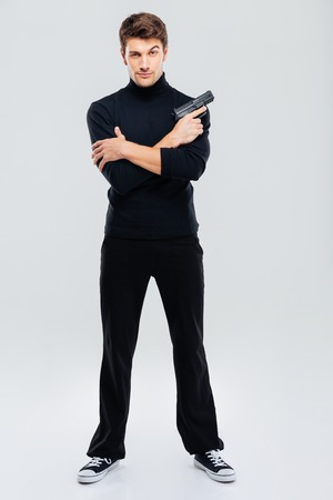 Serious attractive young man standing and holding gun