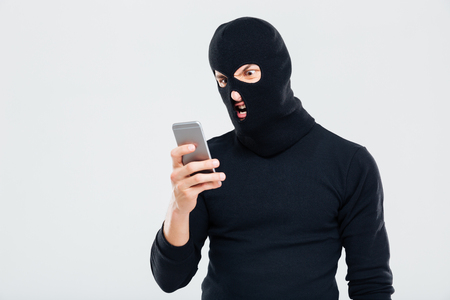 Angry young man in balaclava using cell phone