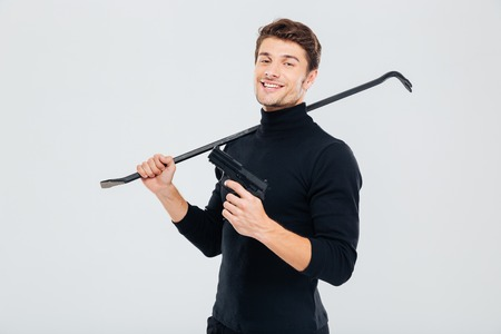 Smiling criminal burglar standing with gun and crowbar