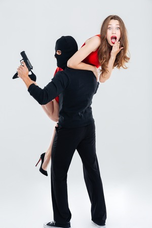 Full length of man in balaclava with gun stealing young woman Stock Photo