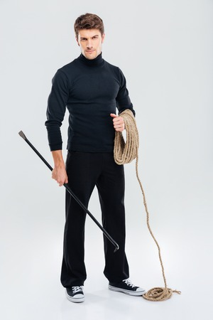 offender: Full length of man offender with rope and crowbar Stock Photo