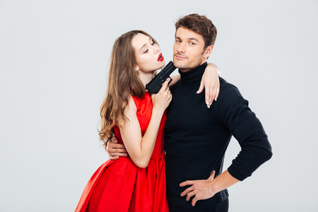 Sensual young couple playing and posing with gun Stock Photo