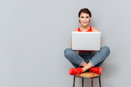Young beautiful smiling girl using laptop pc computer for study isolated on the gray background