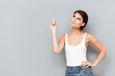 whitem: Serious young woman pointing finger up over gray background