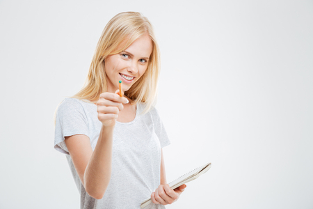 dreaminess: Cute young blonde girl pointing at camera holding notebook over white background Stock Photo