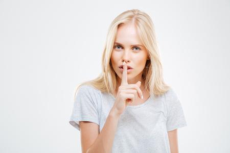 guardar silencio: La mujer rubia que muestra el dedo sobre los labios de backgound blanco