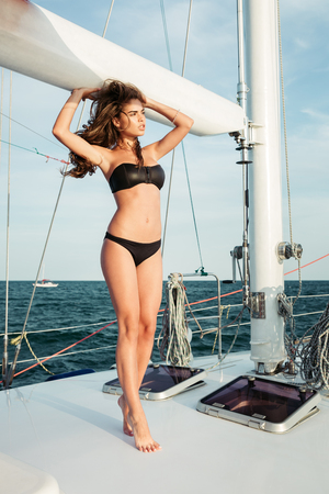 short wave: Young beautiful brunette girl in swimsuit posing on the yacht Stock Photo