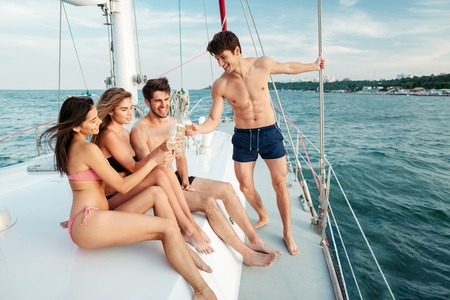 boat party: Group of young happy friends drinking and having party on a sailing boat