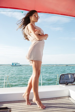 Young beautiful brunette girl in suglasses standing on the yacht Stock Photo