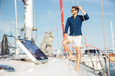 Young stylish sailor man in hat and sunglasses standing on the yacht Фото со стока