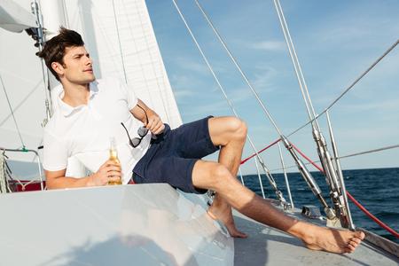 自信を持ってハンサムな若い男、ヨットの上で休んでいる間はビールを飲む