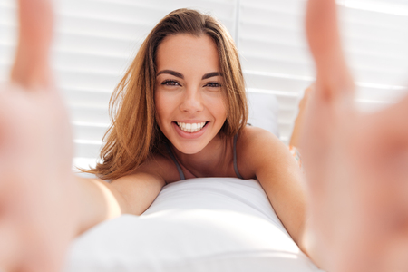 Portrait of a smiling cute woman in bikini making selfie photo on smartphone isolated on a white background 版權商用圖片