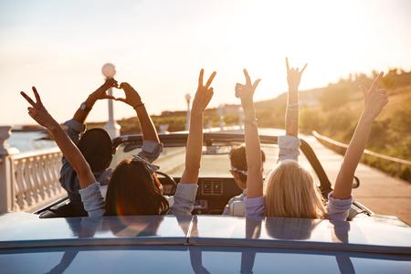 敞蓬车的小组愉快的年轻朋友用驾驶在日落的被举的手