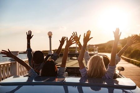 Back view of happy young friends driving cabriolet with raised hands on sunset Stock Photo