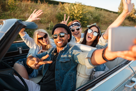 Multiethnic group of happy young people taking selfie with smartphone and showing peace sign in the car Stockfoto
