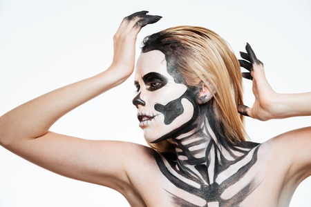 Woman with scared halloween makeup standing and posing over white background