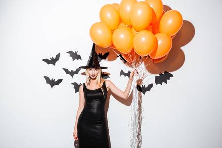 Sexy young woman in witch halloween costume standing and holding bunch of orange balloons over white background Stock Photo