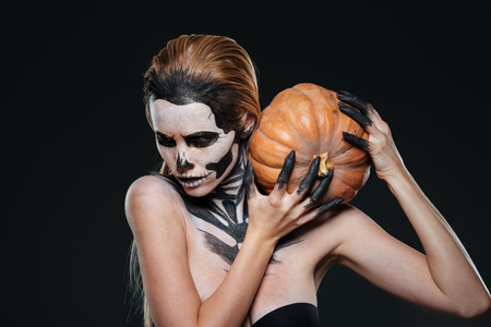 Woman with scared halloween makeup holding pumpkin over black background Stock Photo
