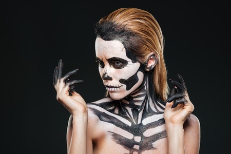 Portrait of girl with fearful halloween makeup over black background