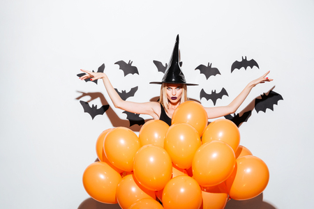 Gothic young woman in witch hat standing with raised hands behind orange balloons over white background