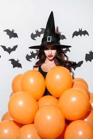 Attraktive junge Frau in Hexenkostüm Kostüm mit orange Ballons über weißem Hintergrund