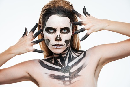 terrifying: Closeup of woman with gothic terrifying makeup posing over white background