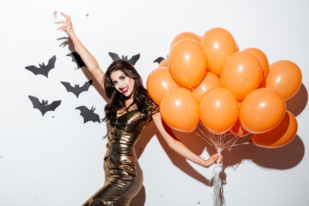 Cheerful young woman with scaring vampire makeup and bunch of orange balloons having fun over white background