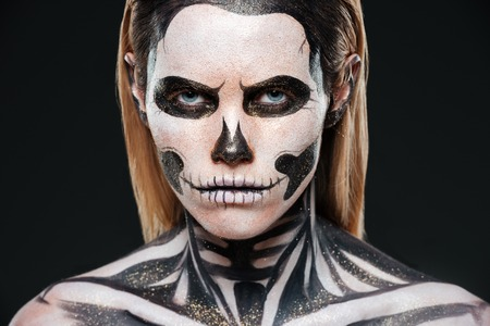 terrifying: Closeup of young woman with terrifying skeleton makeup over black background