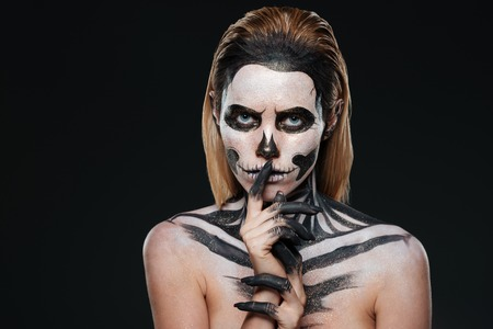Woman with scared halloween makeup showing silence gesture over black background Stock Photo