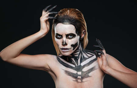 terrifying: Woman with gothic terrifying makeup posing over black background