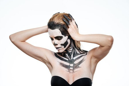 Portrait of young woman with frightening halloween makeup posing over white background Stock Photo