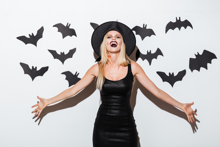 Beautiful blonde young woman in witch costume standing and laughing over white background Stock Photo