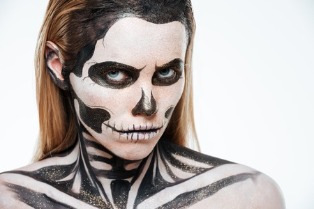 terrifying: Woman with terrifying skeleton makeup over white background