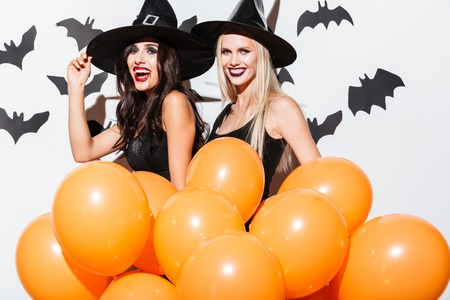 Two happy young women in black witch halloween costumes with orange balloons laughing over white background