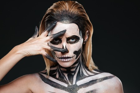 terrifying: Woman with terrifying halloween makeup over black background