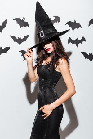 Sexy gotische jonge vrouw in zwarte heks halloween kostuum met hoed die zich voordeed op witte achtergrond