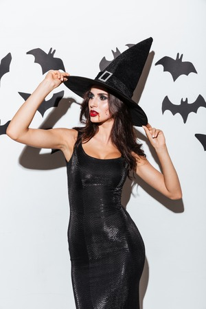 marquise: Portrait of beautiful young woman in black witch halloween costume with hat over white background