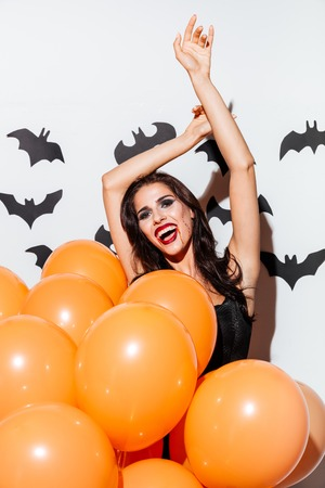 Sexy brunette girl in black halloween dress posing with bunch of orange balloons isolated on the white background Stock Photo