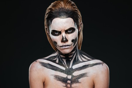 terrifying: Angry young woman with gothic halloween makeup over black background
