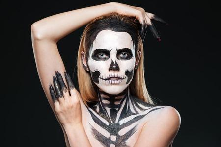 living skull: Portrait of girl with scared skeleton makeup over black background Stock Photo