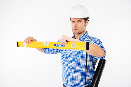 Serious young man building engineer in hard hat using spirit level Stock Photo