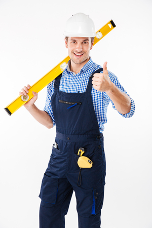 Full length portrait of a smiling male builder standing and showing thumbs up gesture isolated on a white background