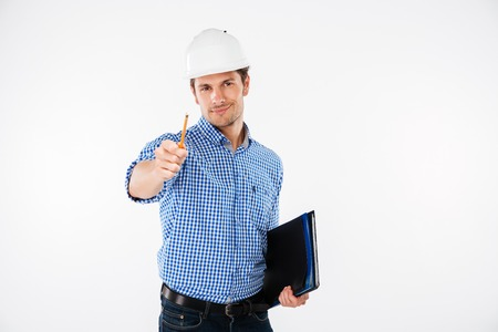 Happy young man architect in hard hat holding folder and pointing on you
