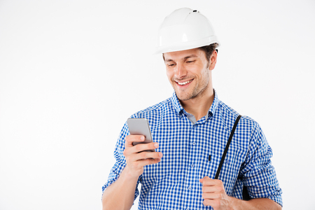 Smiling young man builder in hard hat using mobile phone